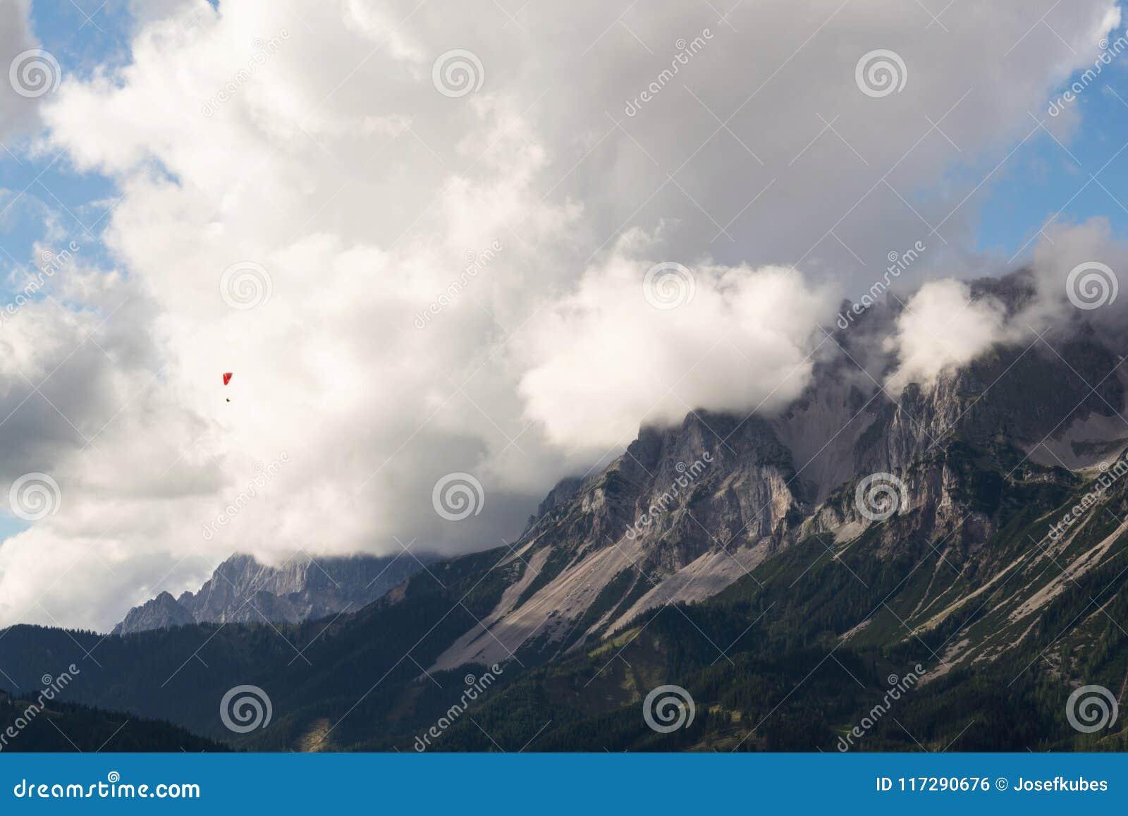 Paraglider que voa sobre Schladming, fundo das montanhas de Dachstein, cumes, Áustria