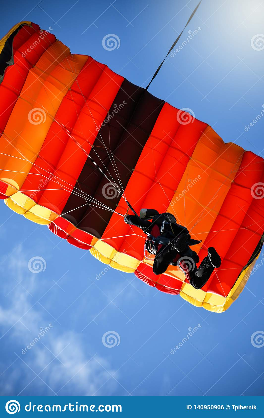 Paraglider With Red Parachute Flying In The Blue Sky Stock ...