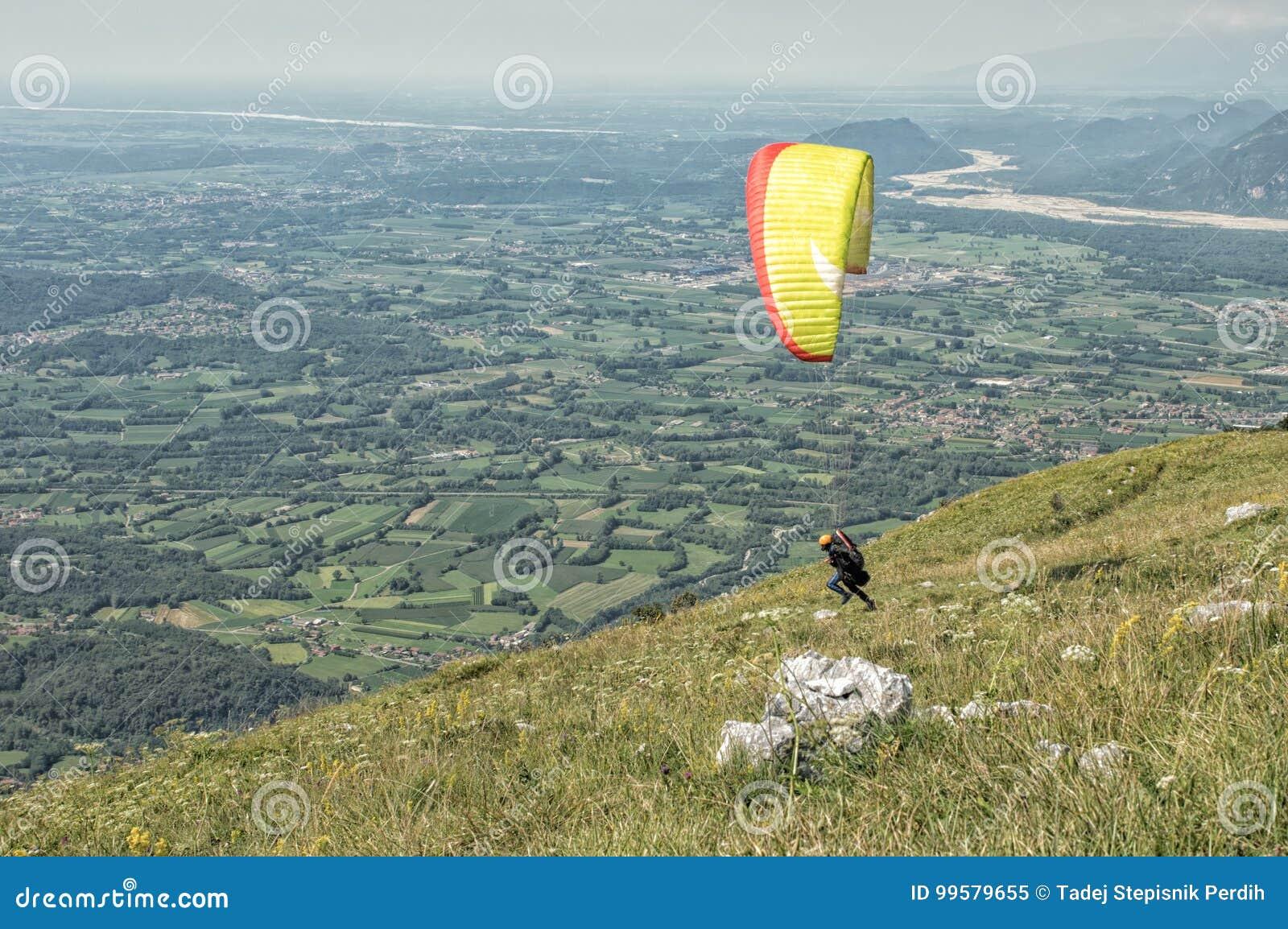 Paraglider som startar ett flyg över kullarna på en solig dag