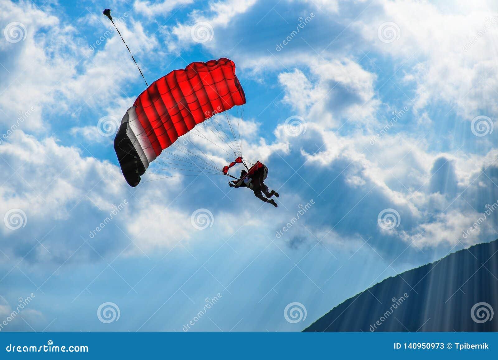 Paraglideren med rött hoppa fallskärm flyg i den blåa himlen