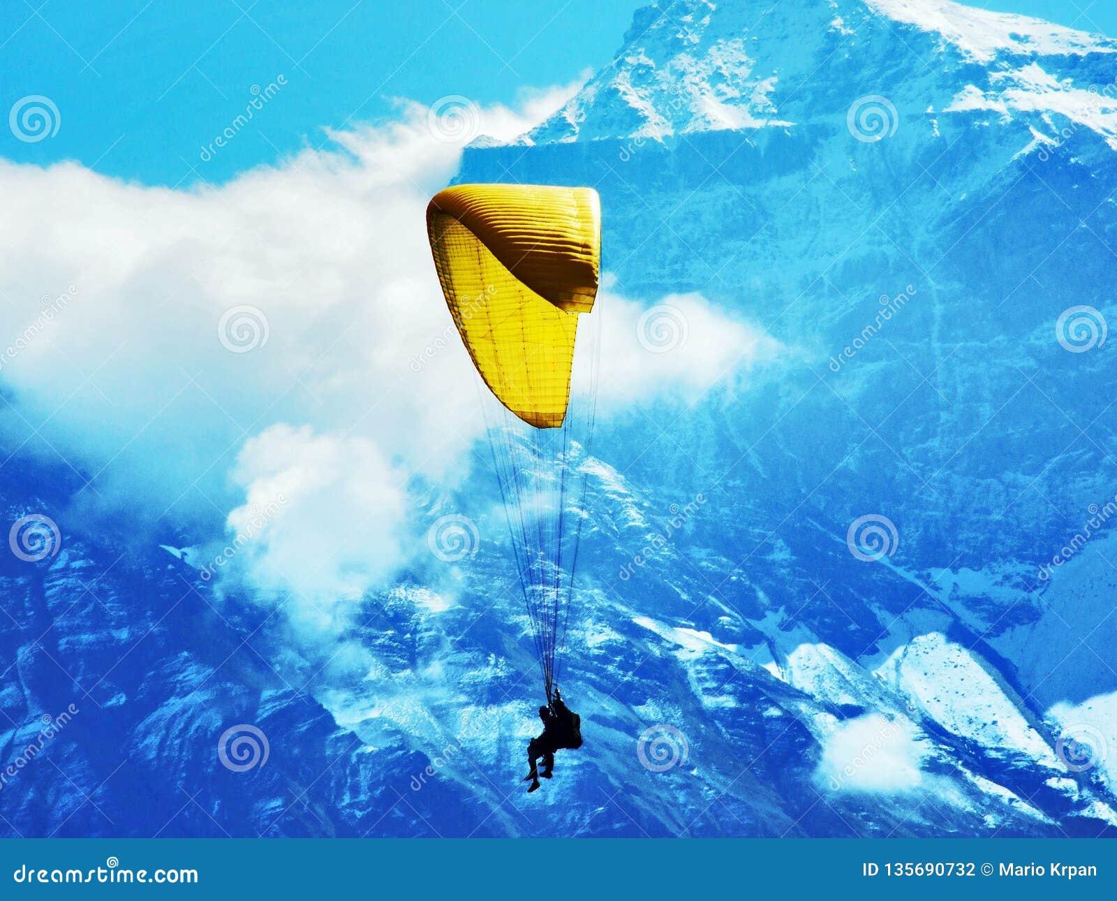 Paragliders em tandem nos cumes de Glarus da cordilheira ou na região de turista de Glarnerland