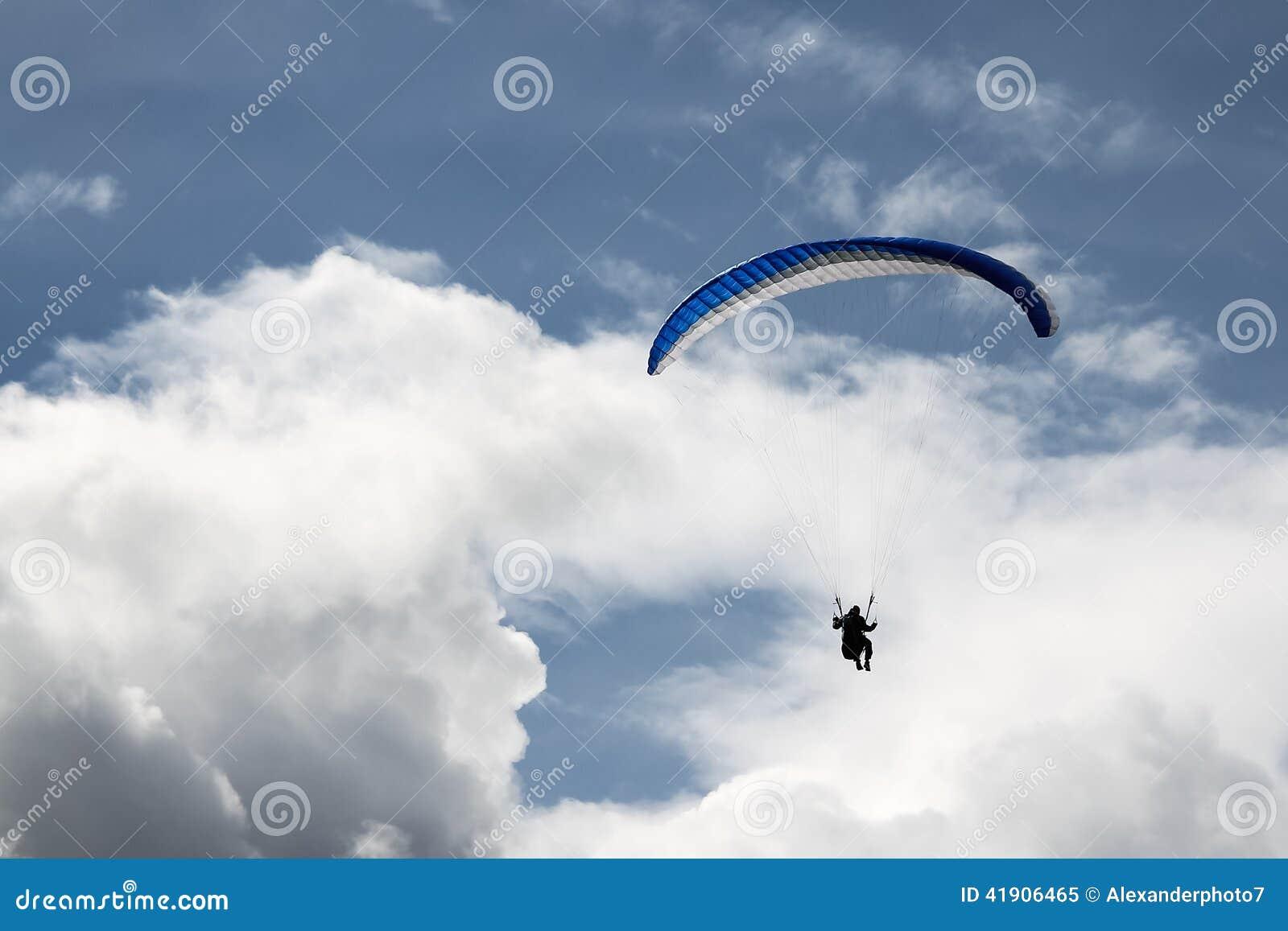 Paragliding en los cielos nublados azules