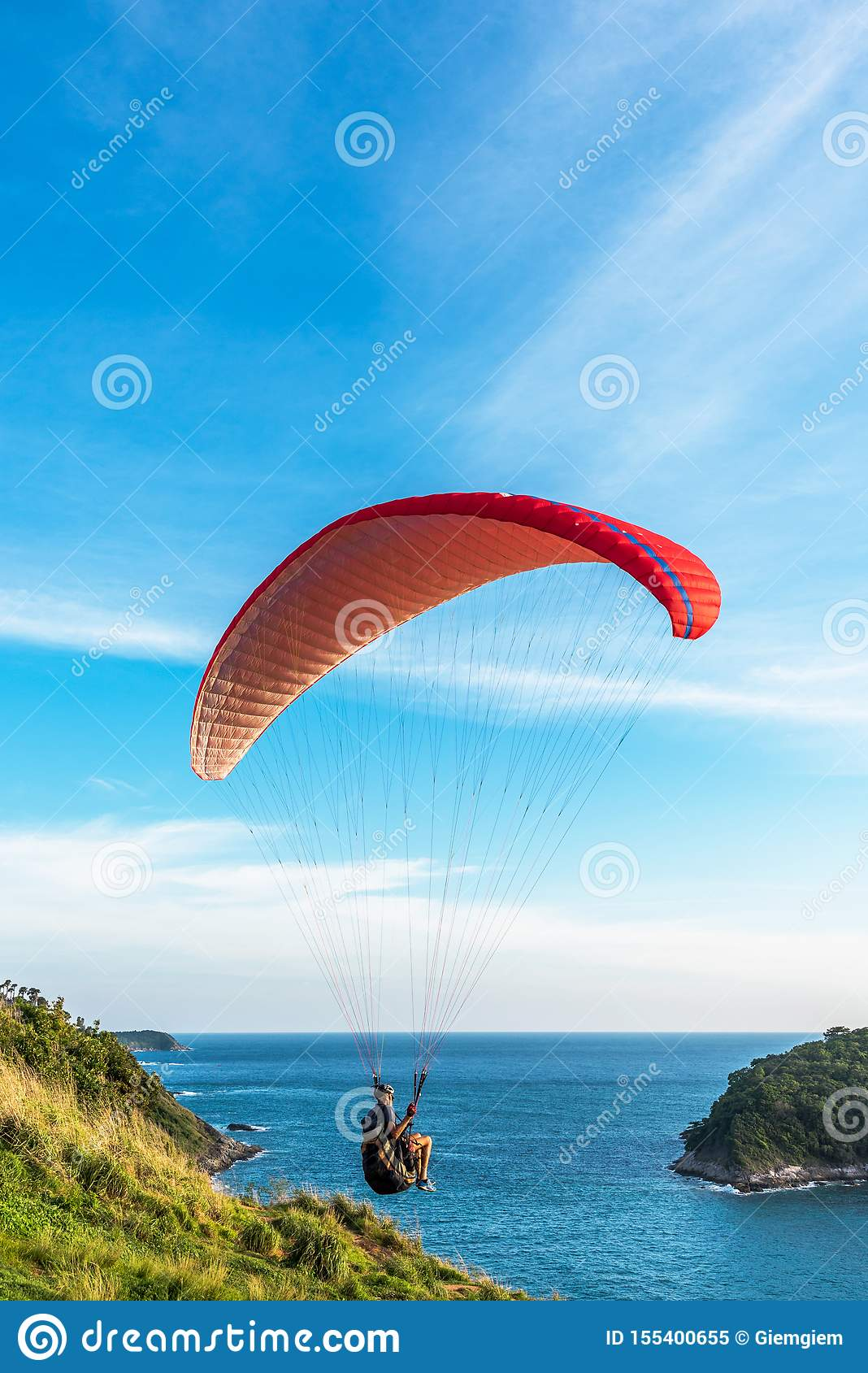 Paragliding Extreme sport, Paraglider flying on the blue sky and white cloud in Summer day at Phuket Sea, Thailand