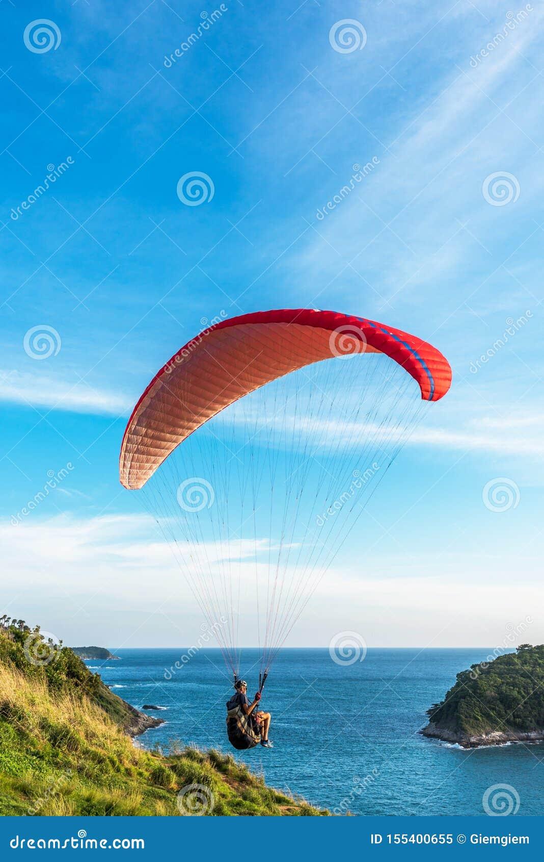 Paragliding Krańcowy sport, Paraglider latanie na niebieskim niebie i biel, chmurniejemy w letnim dniu przy Phuket morzem, Tajlan