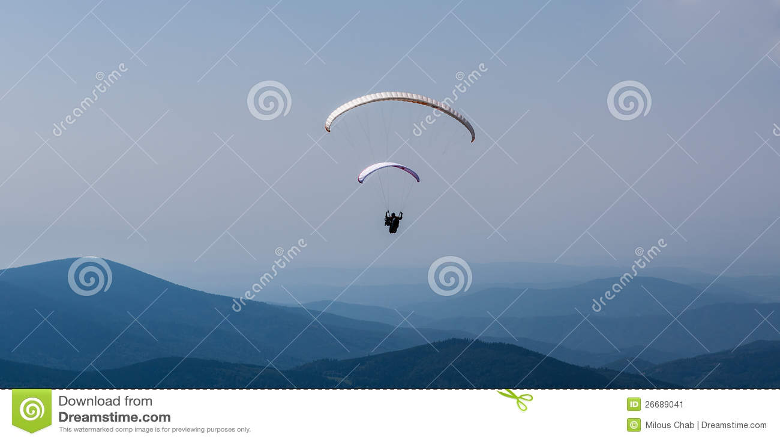 Paragliding sobre a montanha de encontro ao céu azul