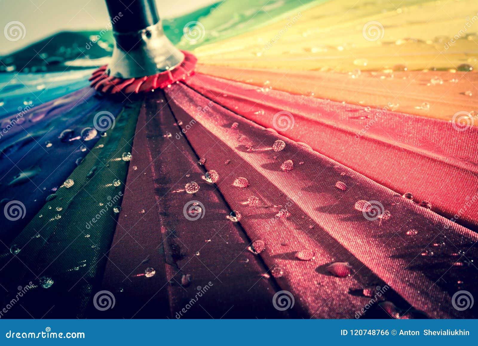 Paraguas colorido multicolor con todos los colores del arco iris con las gotas de agua