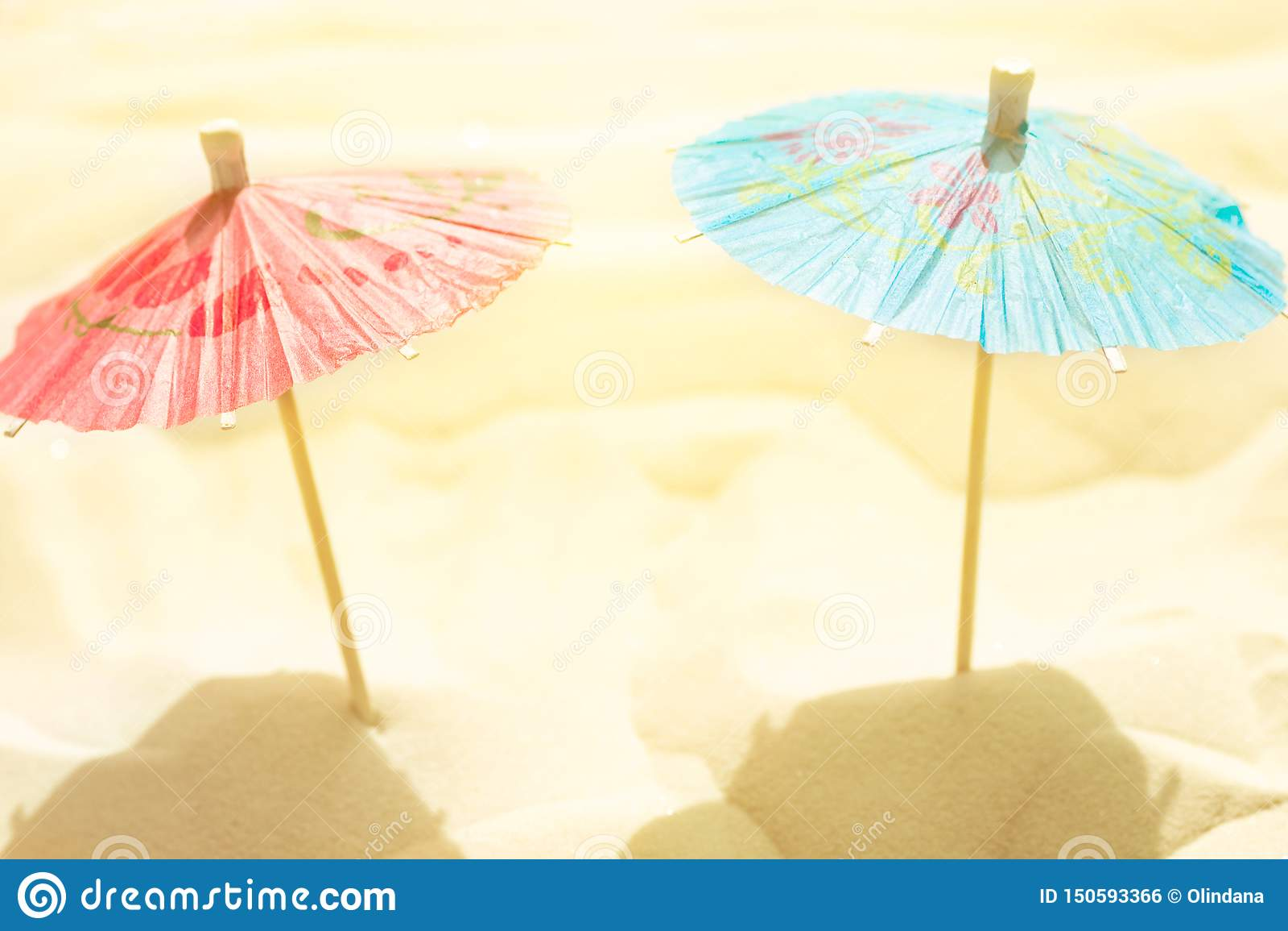 Paraguas de papel del cóctel en la arena de la playa en luz del sol de oro Imagen estilizada artística creativa Relajación de las
