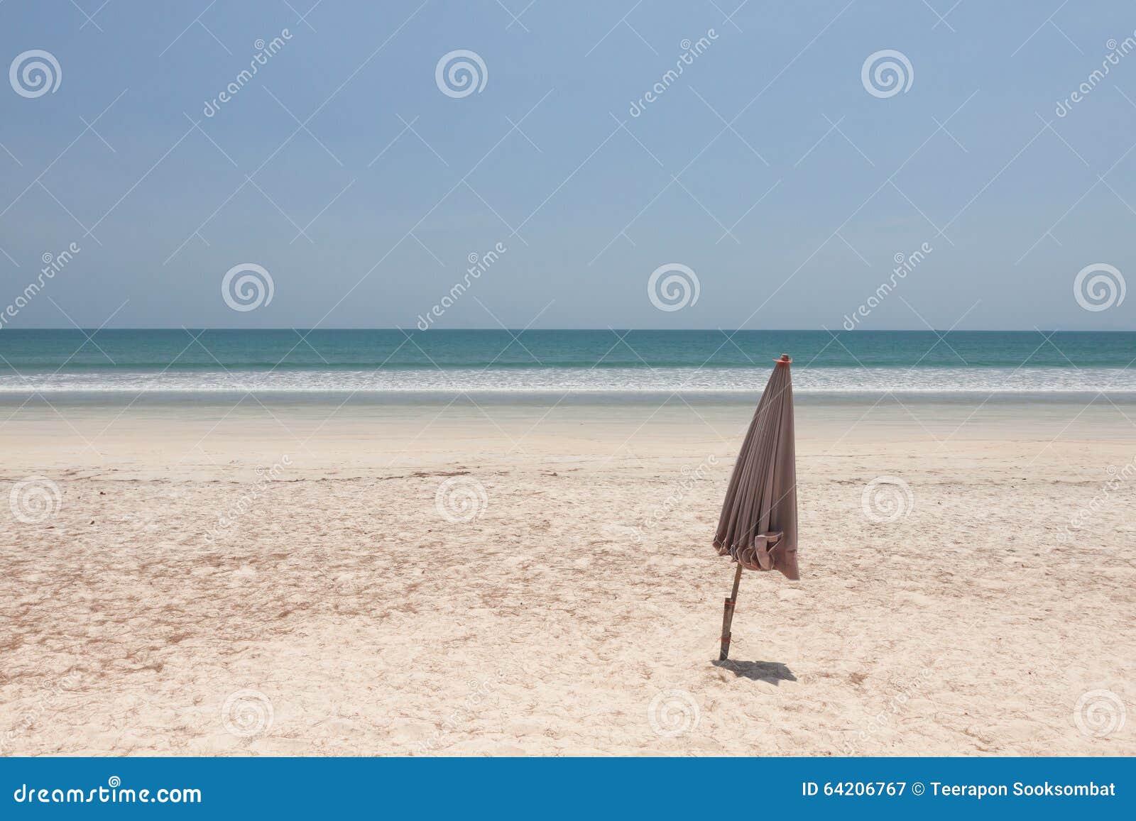 Paraguas doblado en la playa