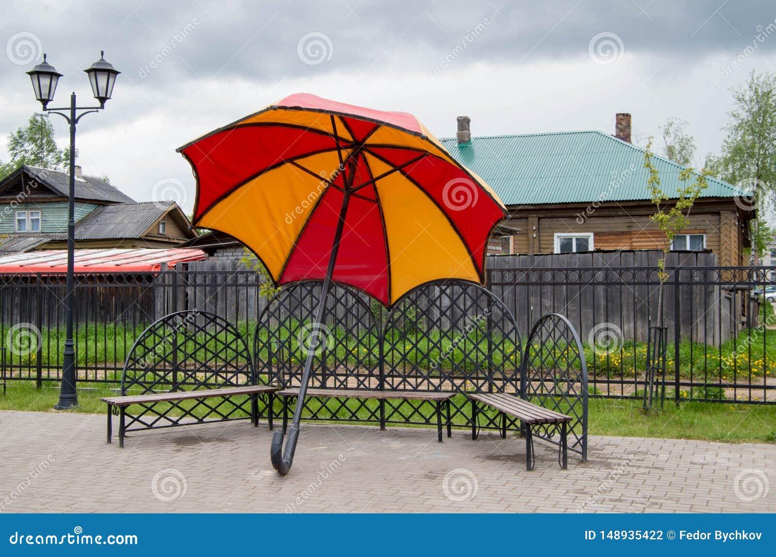 Paraguas gigante al lado de los bancos