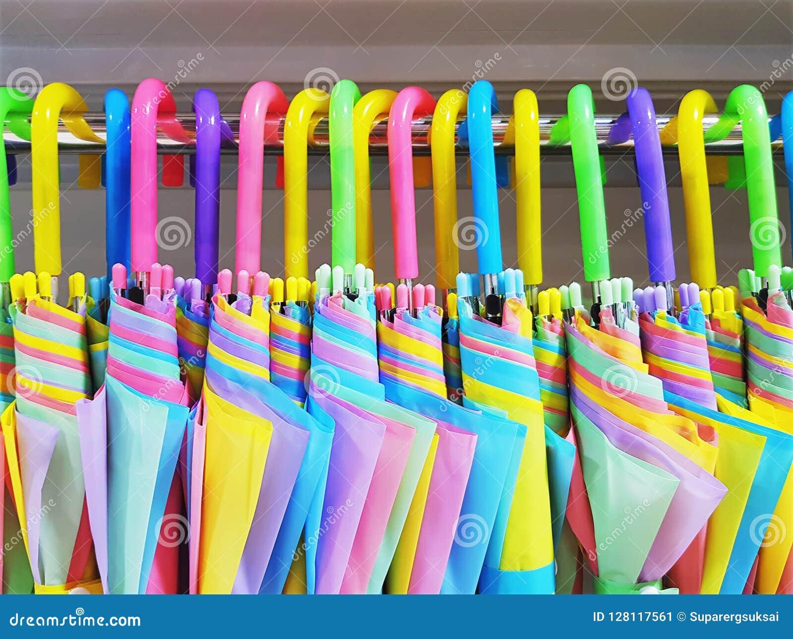 Paraguas vibrantes coloridos que cuelgan en el estante