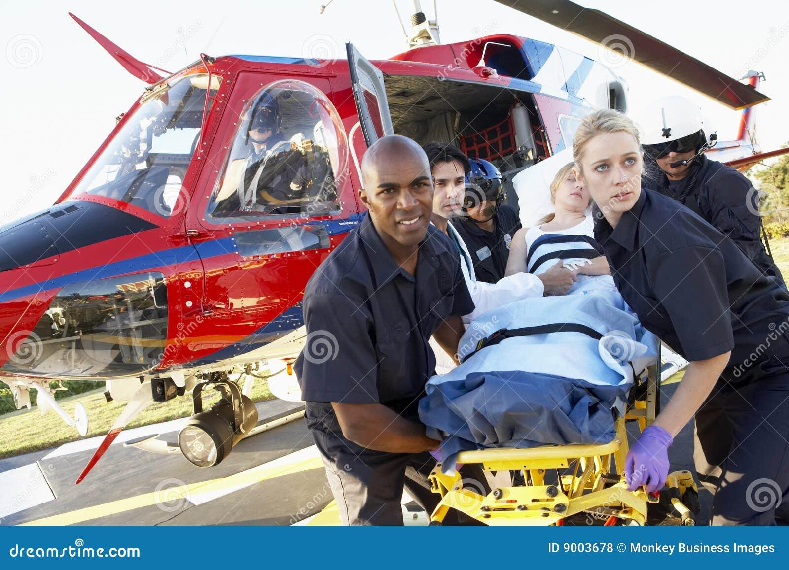 Paramédicos que descargan al paciente del helicóptero
