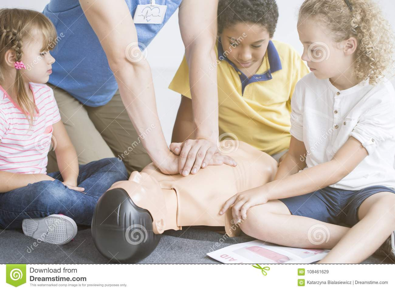 Paramedic showing children chest compressions