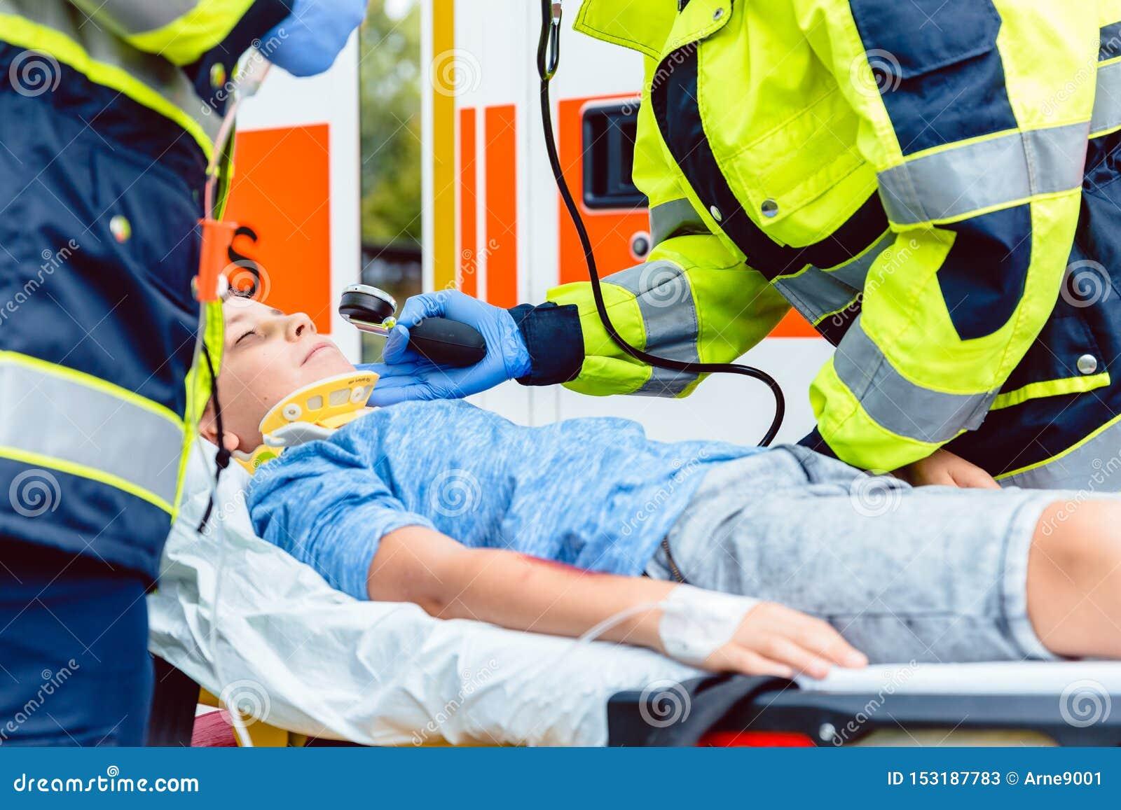 Paramedici che misurano pressione sanguigna del ragazzo danneggiato