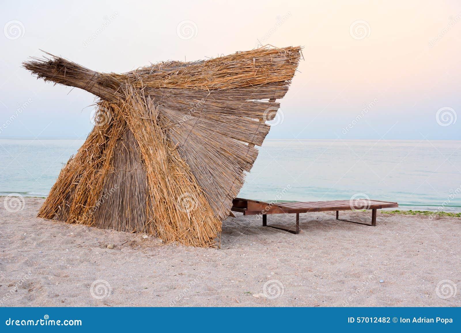 Parapluie de Reed sur la plage dans le coucher du soleil