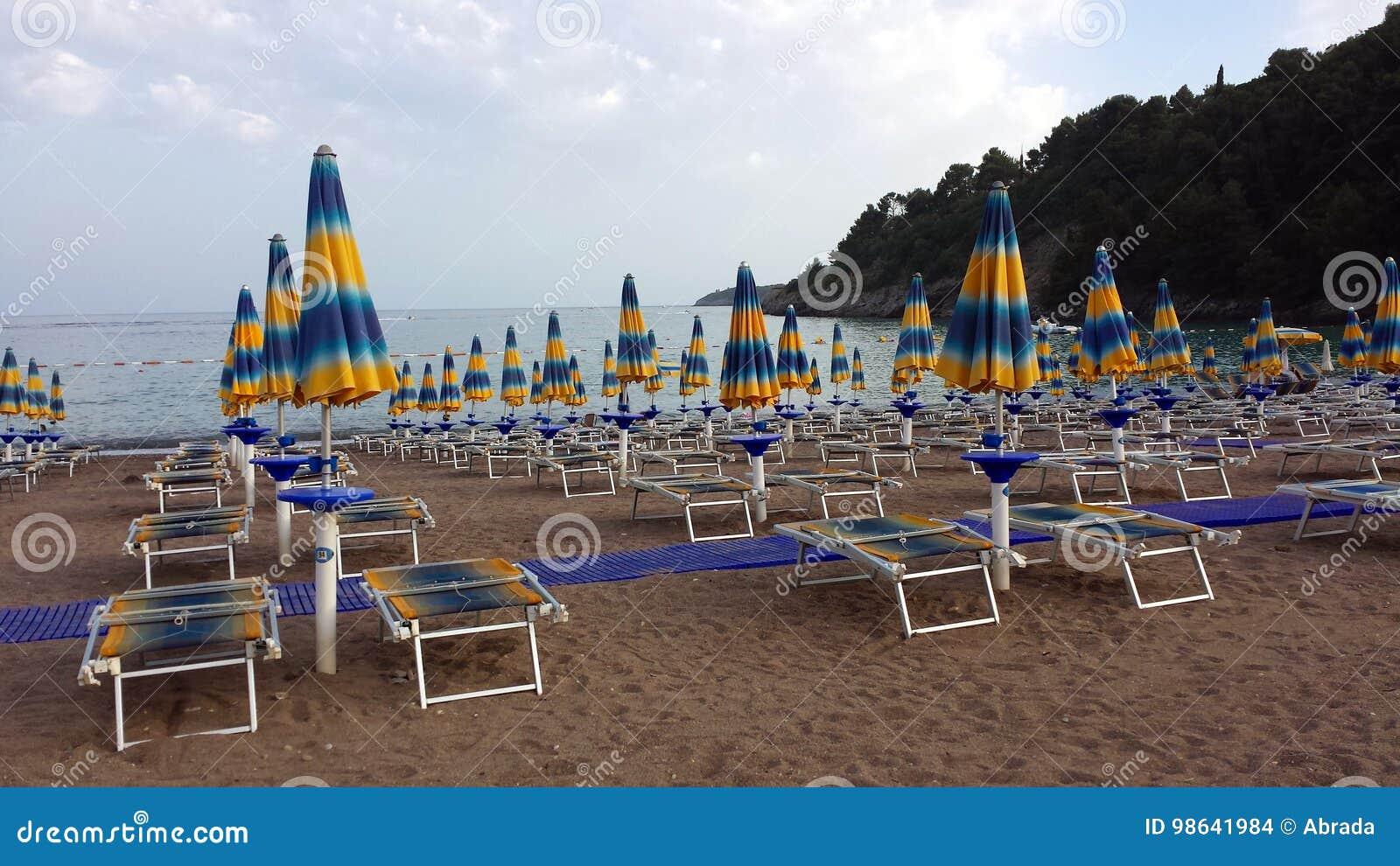 Parapluies et canapés du soleil sur la plage