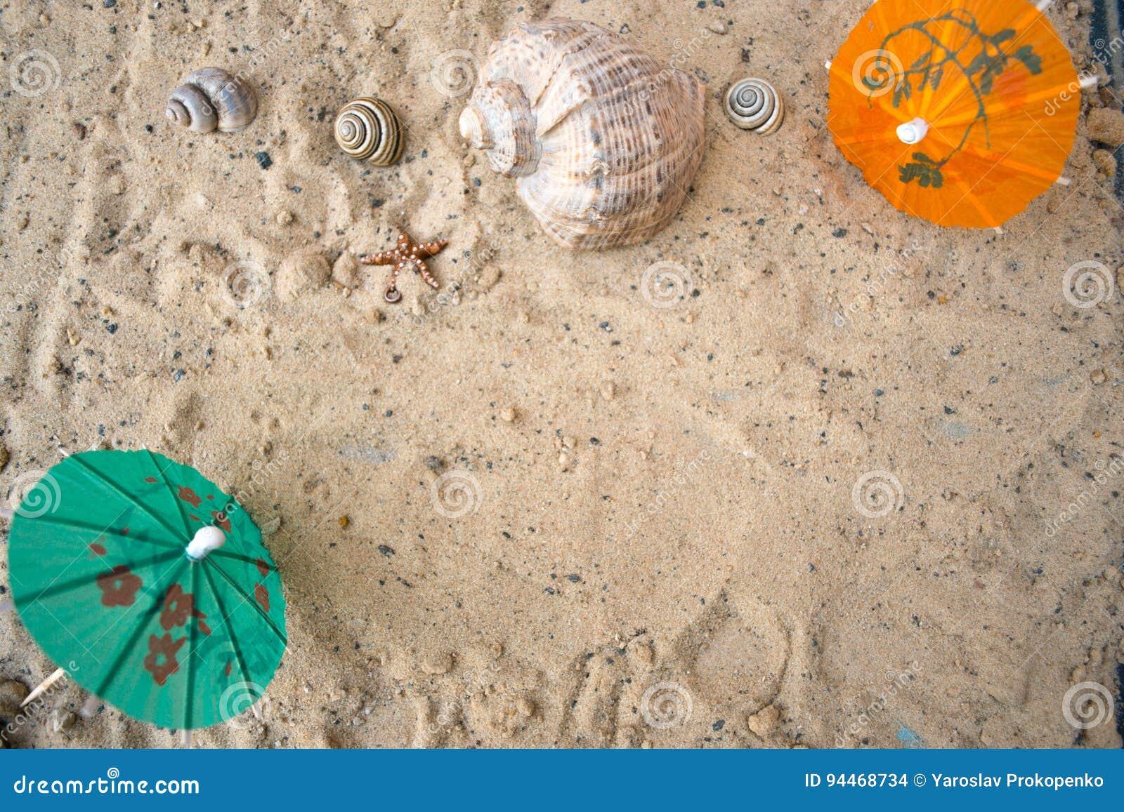 Paraply för coctailar på en sandig sommarbakgrund