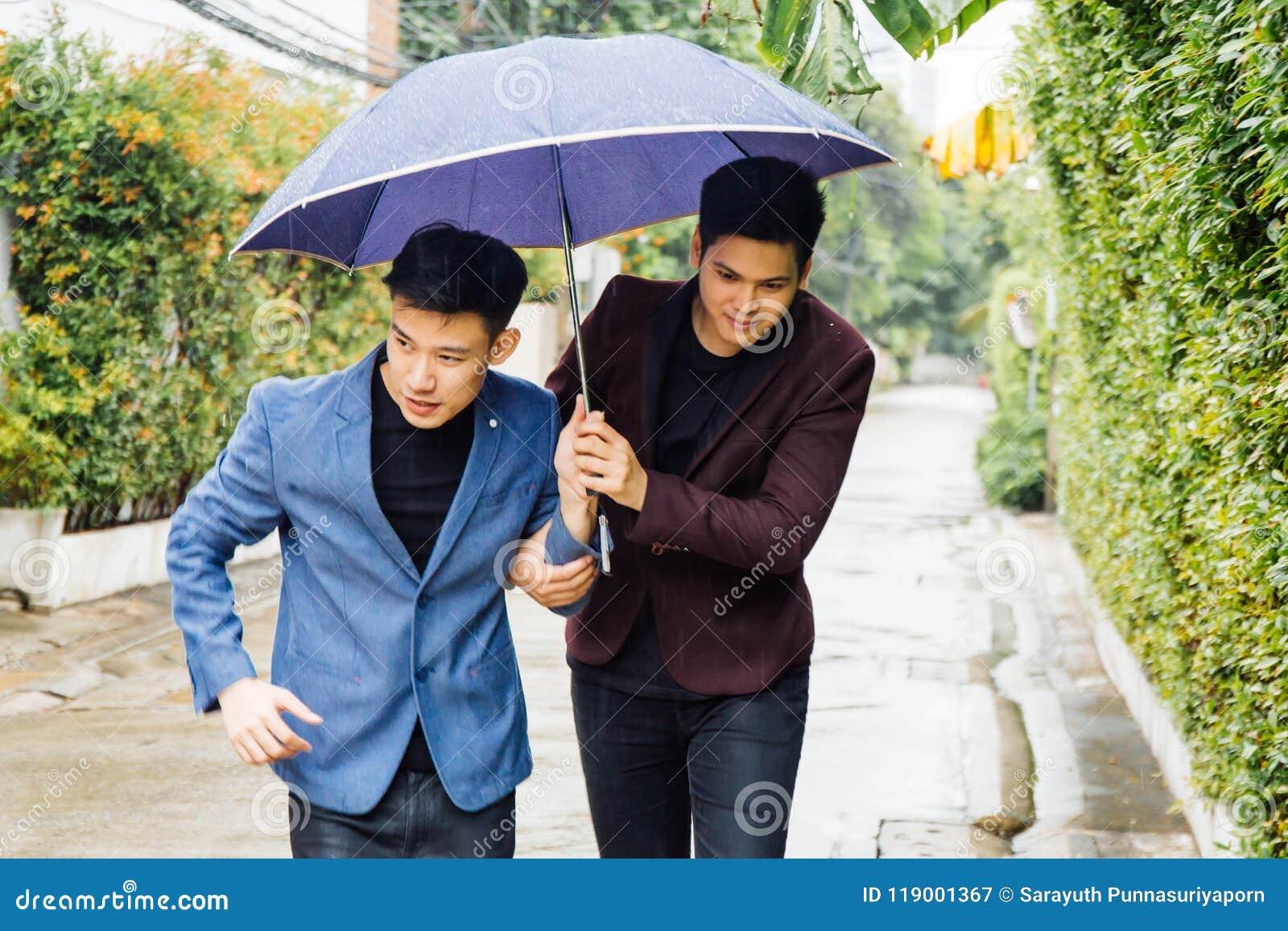 Paraply och händer för glade par hållande tillsammans Asiatiska homosexuella män som går i regnet