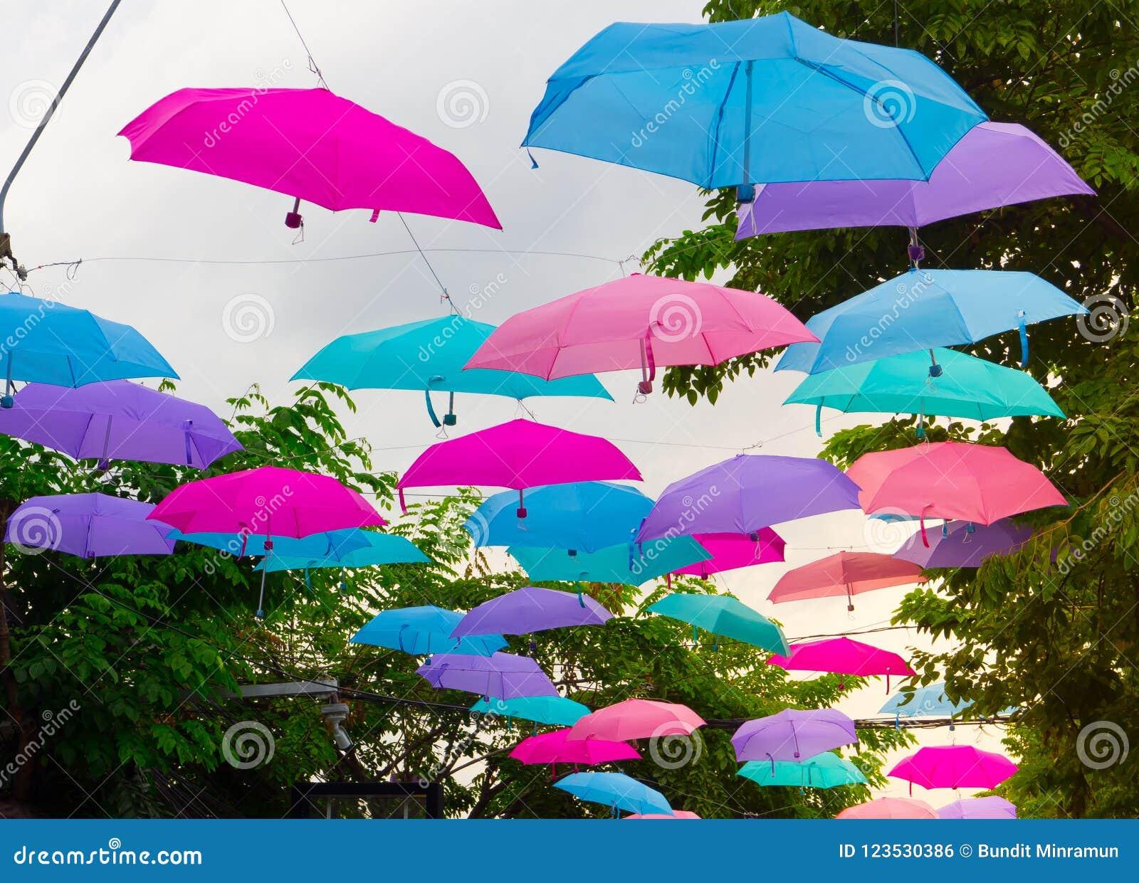 Paraplyet för för för sexhörningsformblått som, rosa färger och lilor hänger längs vägen för offentligt, parkerar garnering