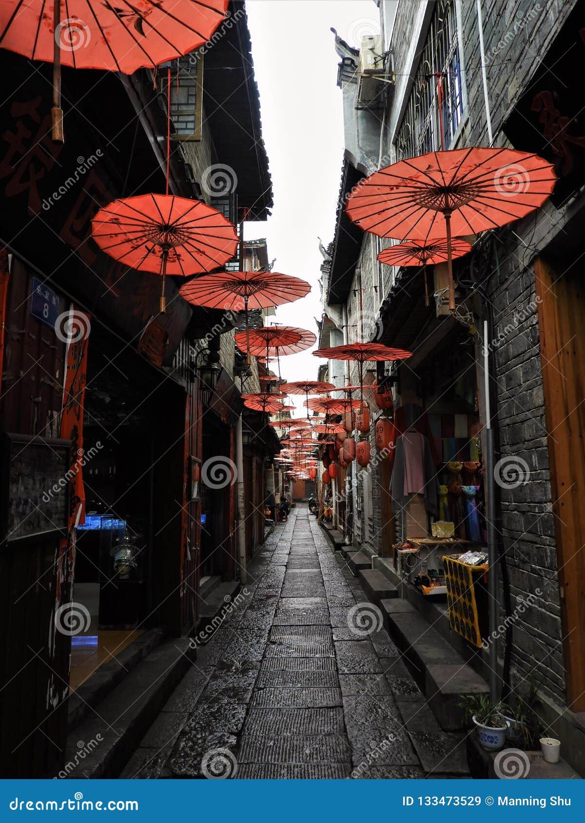 Parasóis vermelhos que penduram sobre a aleia em China