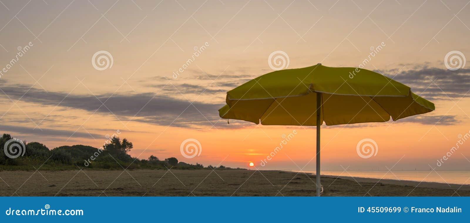 Parasol na plaży przy zmierzchem