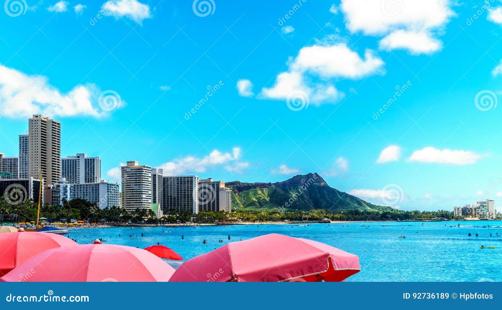 Parasole galore przy Waikiki plażą z swój wiele kurortami pod niebieskim niebem