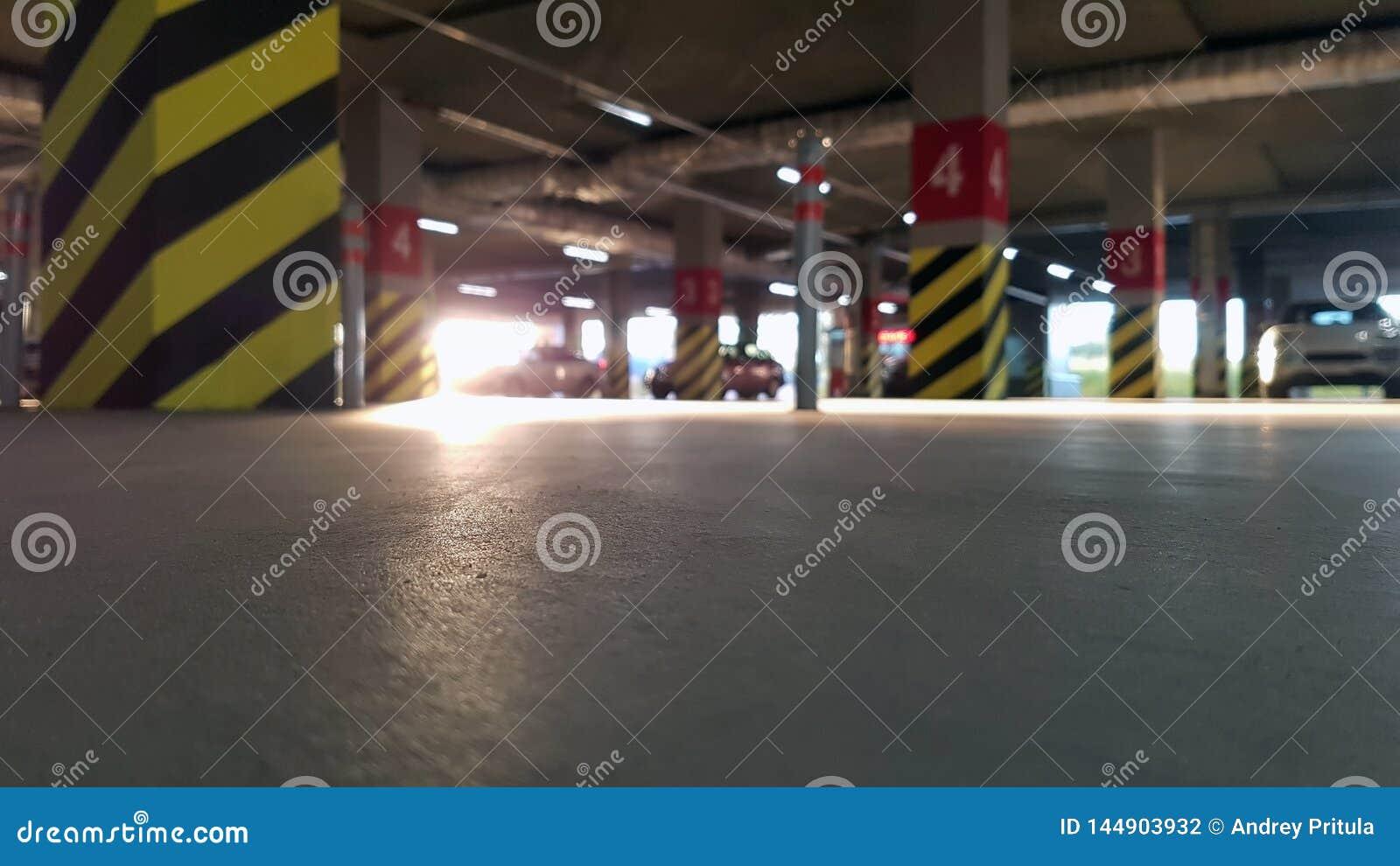 Parcheggio sotterraneo con le automobili un giorno soleggiato