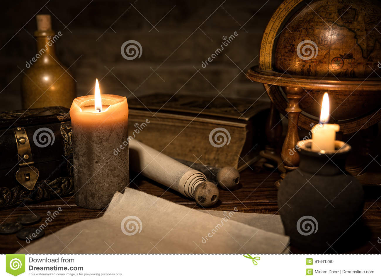 parchment paper, a old globe and candles, a old book and a wooden box, concept medieval background