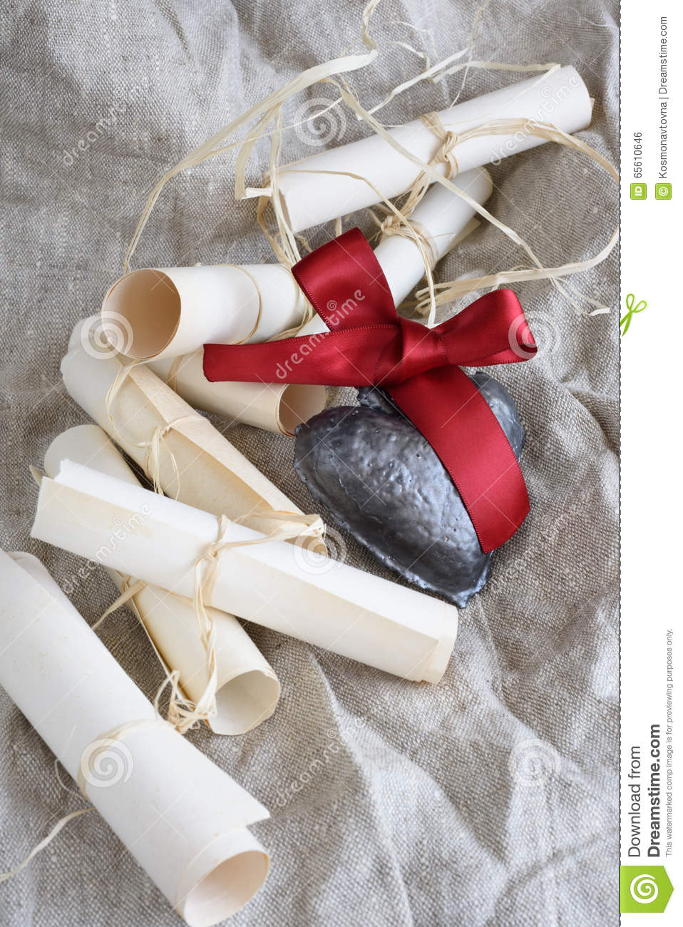 parchment wedding scrolls and ceramic heart with crimson ribbon on a