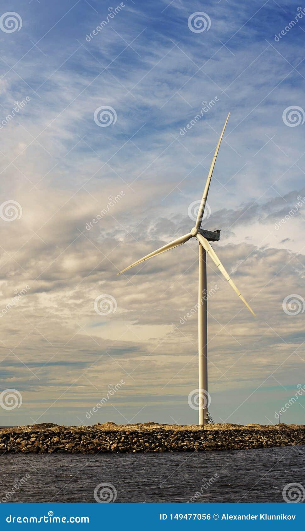 Parco eolico alto bianco sui precedenti del cielo vicino al mare Bothnia del nord