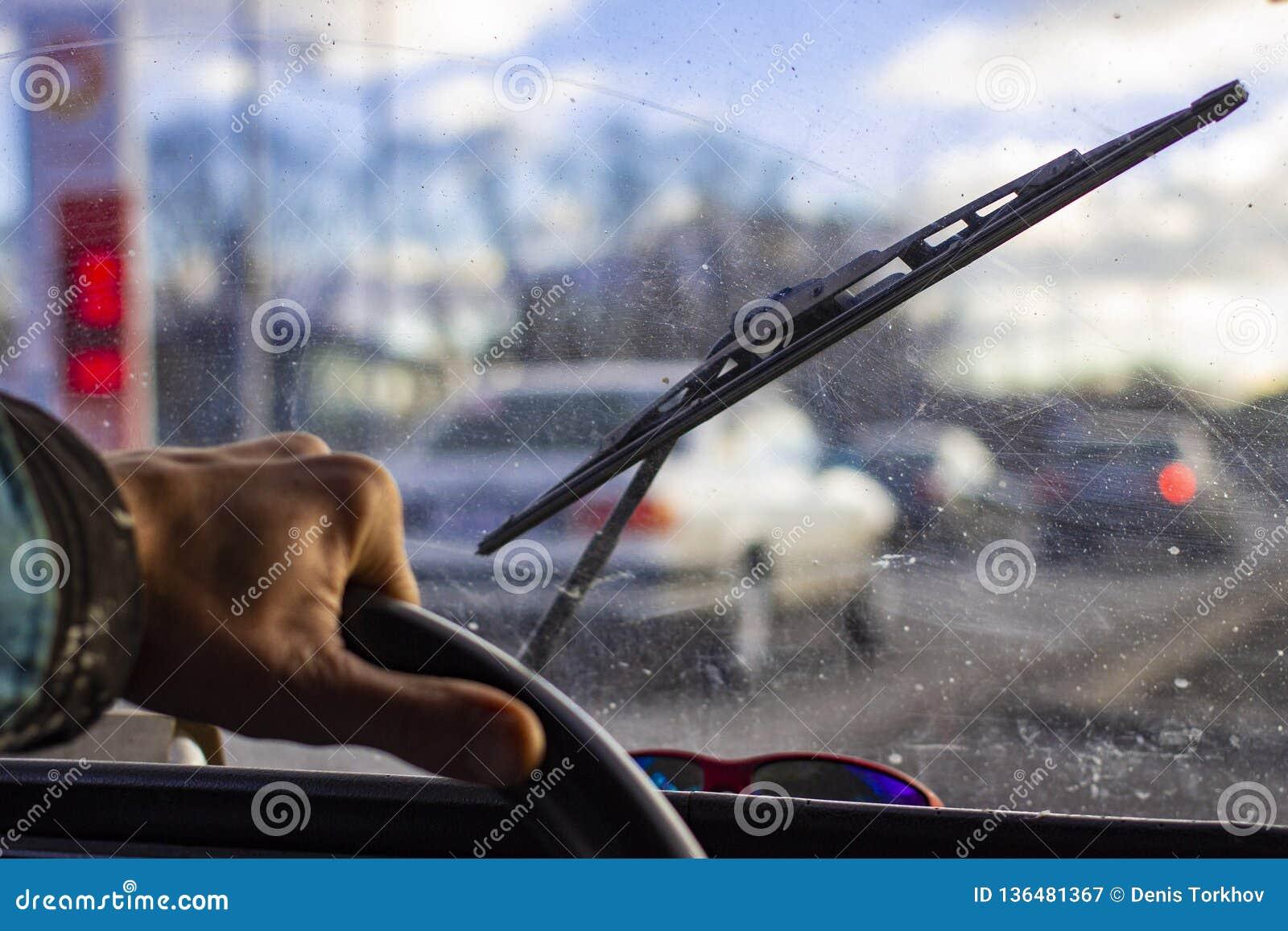 Pare-brise rayé sale de voiture avec l essuie-glace par le volant brouillé avec la main du conducteur sur le fond brouillé