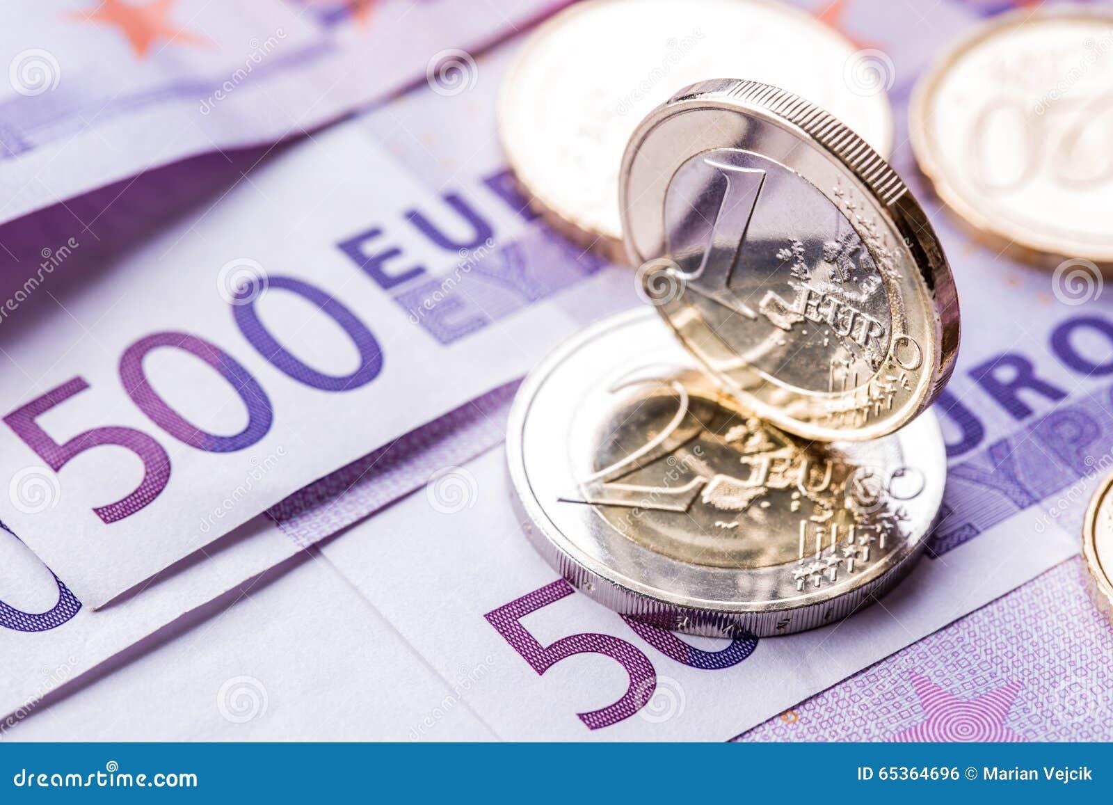 Parecchie 500 euro banconote e monete sono adiacenti Foto simbolica per wealt Euro moneta che equilibra sulla pila con fondo del