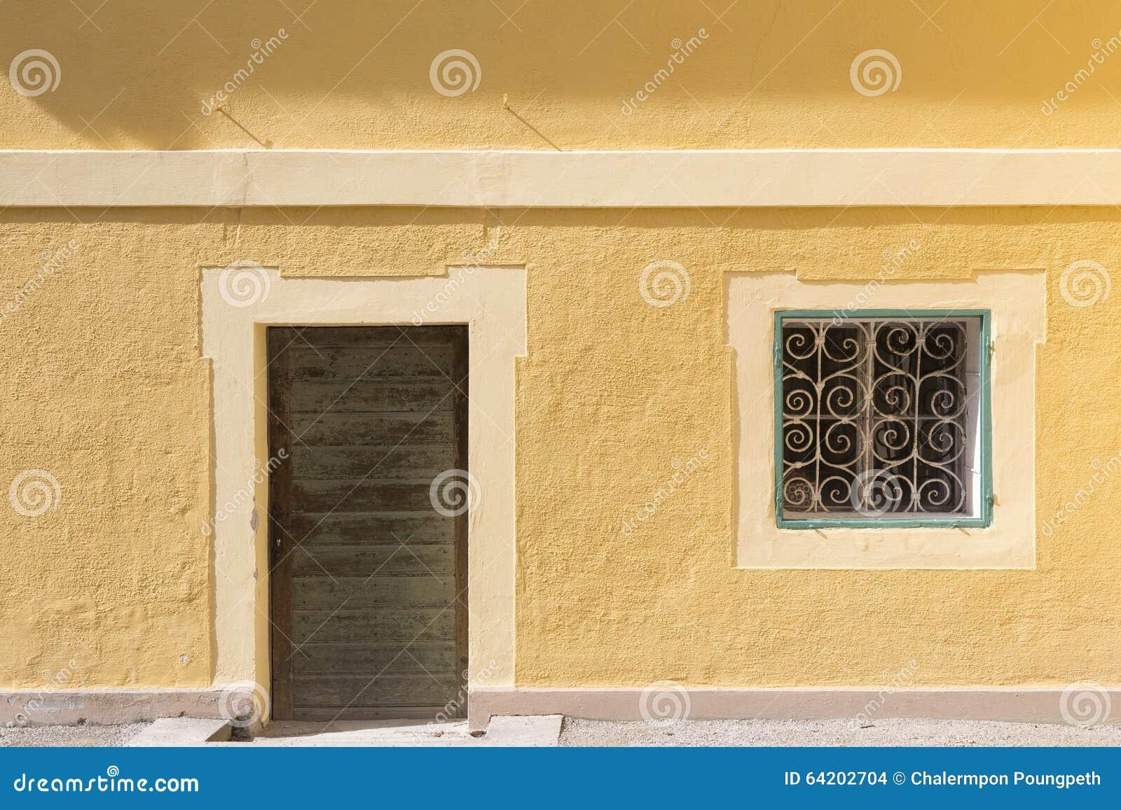 Pared amarilla con la puerta y la ventana