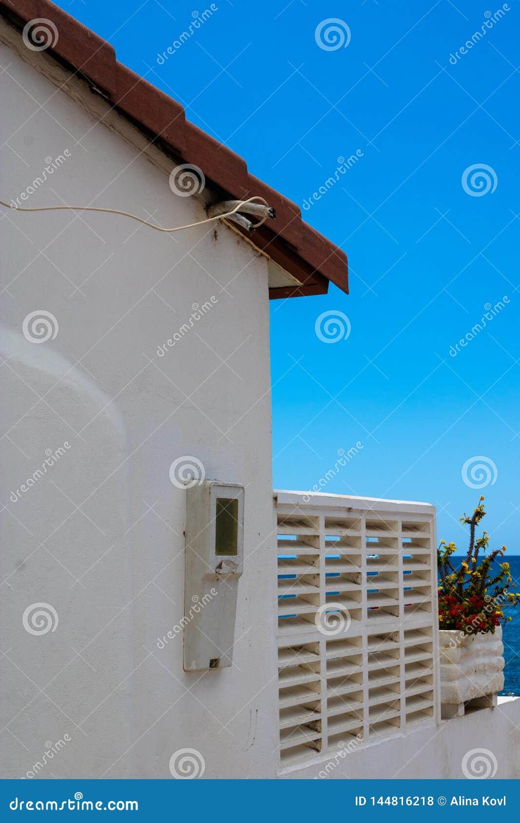 Pared blanca de la casa con los alambres y el fondo del océano - imagen de la electricidad