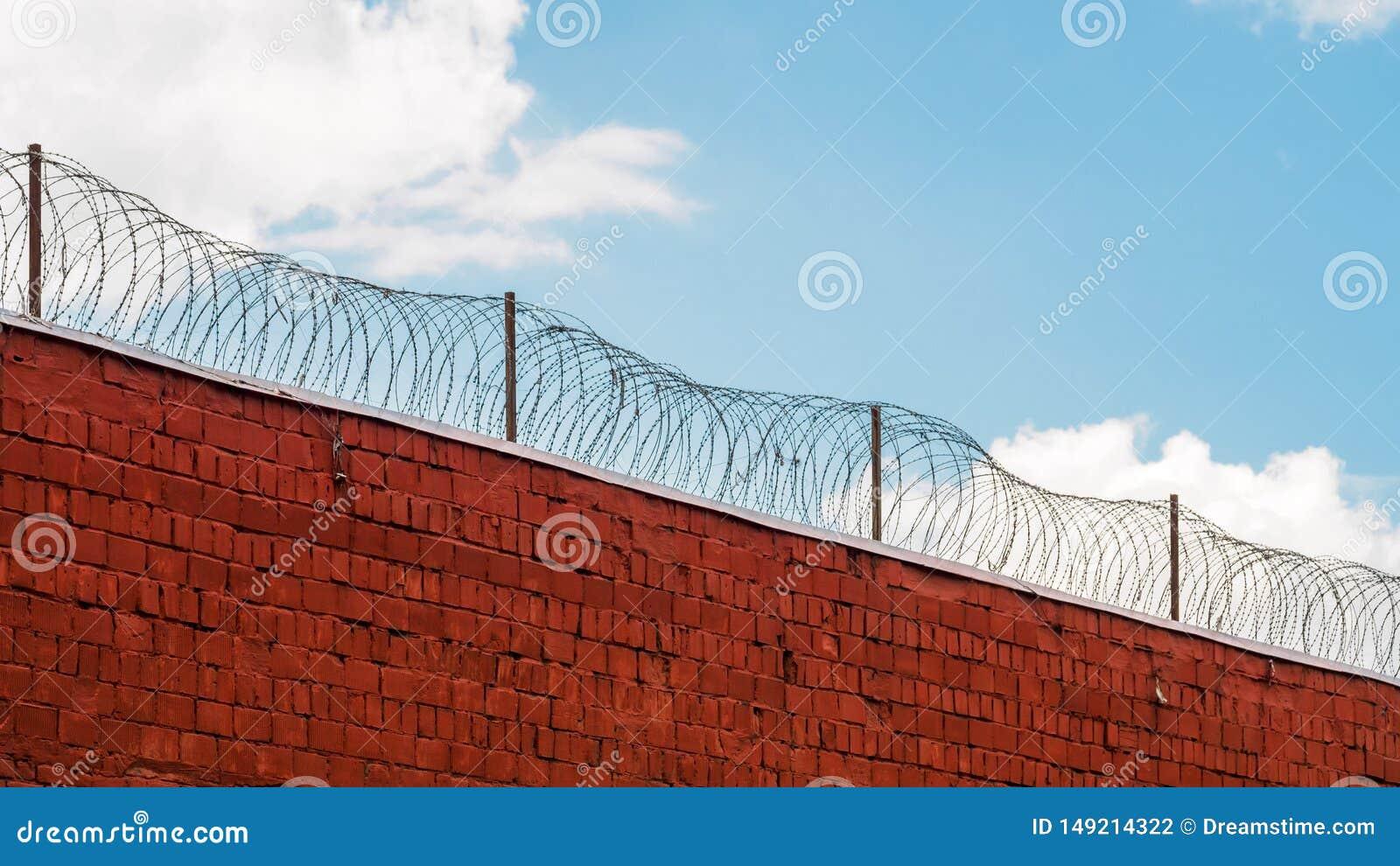 Pared de la prisión con alambre de púas y nubes en el fondo