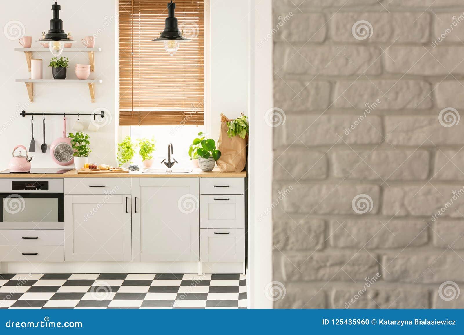 Pared de ladrillo gris en interior brillante de la cocina con las lámparas sobre coun