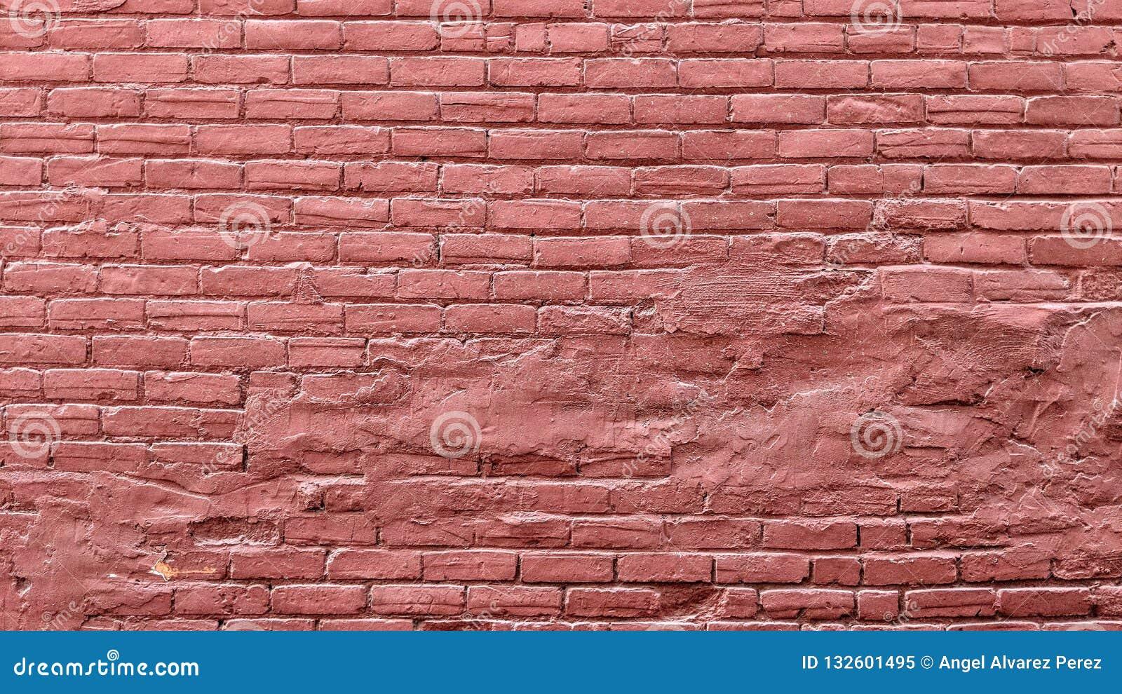 Pared de ladrillo vieja del grunge pintada en rojo
