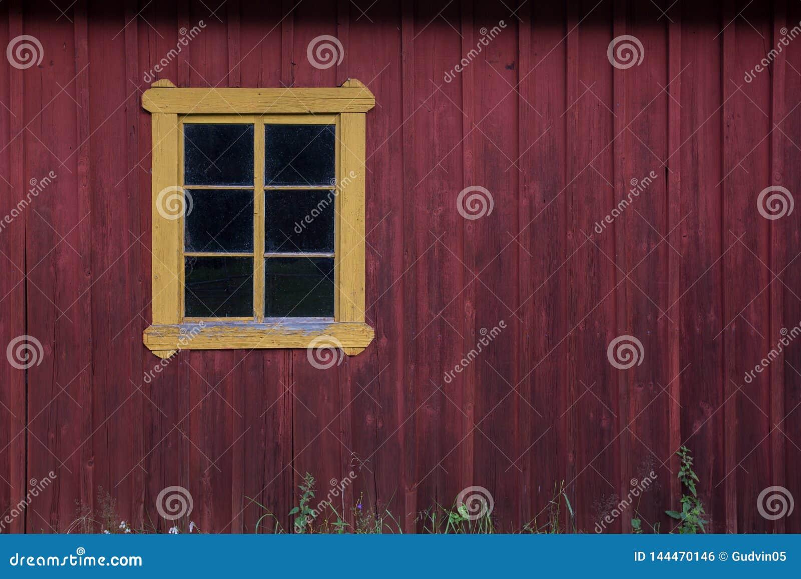 Pared de madera roja con la ventana amarilla Copie el espacio