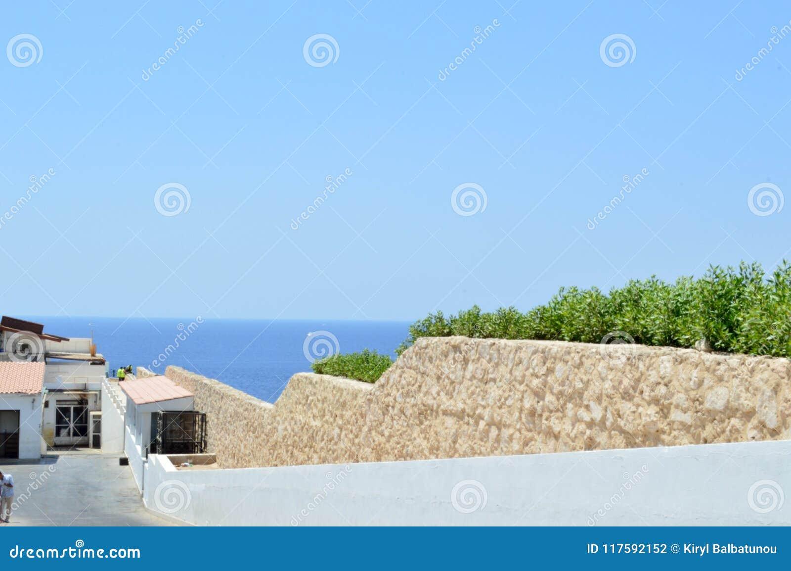 Pared de piedra que desciende abajo al mar con agua azul en un centro turístico tropical y a un edificio blanco con un tejado de