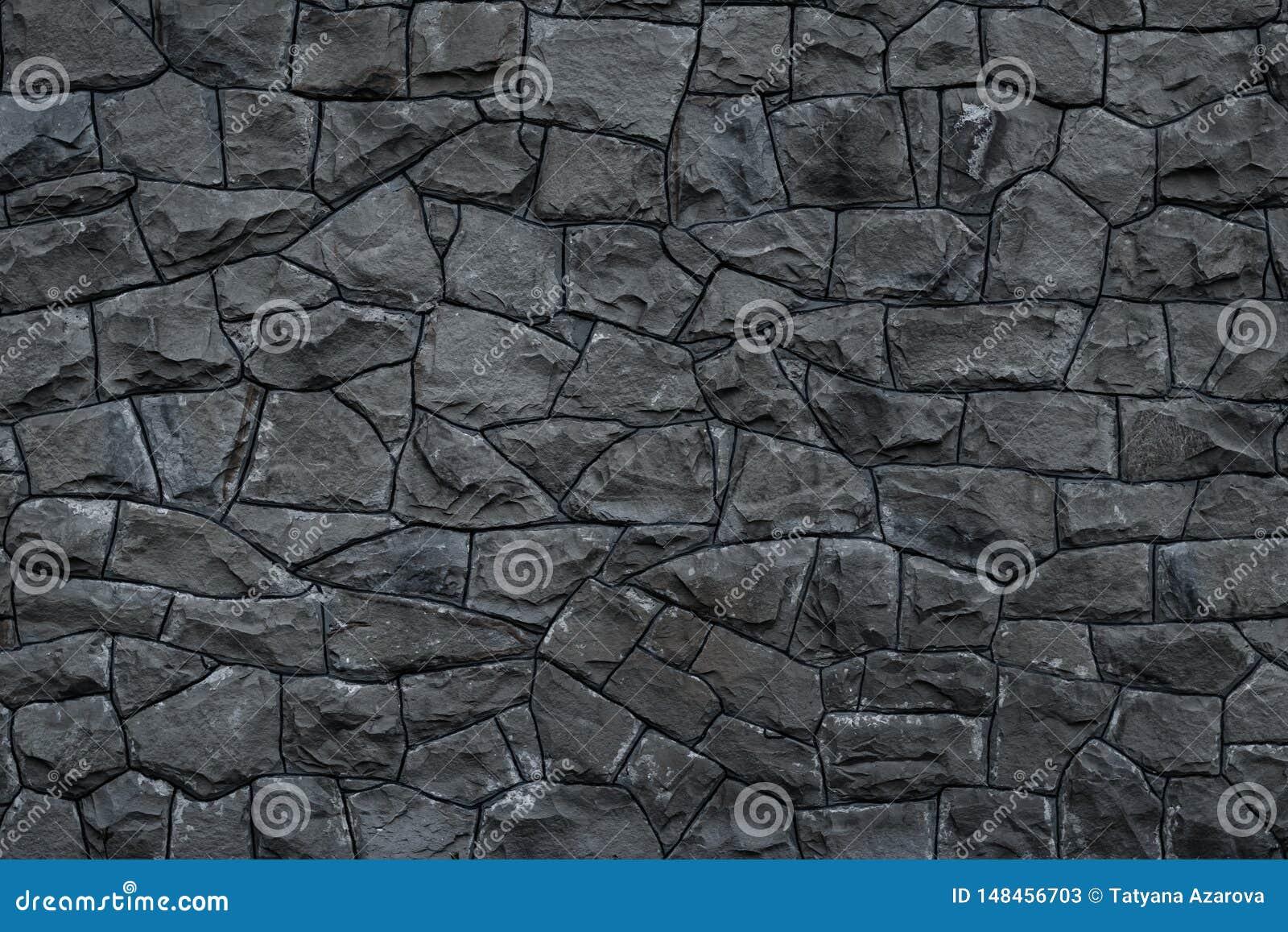 Pared de piedra sucia gris Textura del granito gris Fondo áspero oscuro de las rocas La fachada del edificio gris oscuro resistid