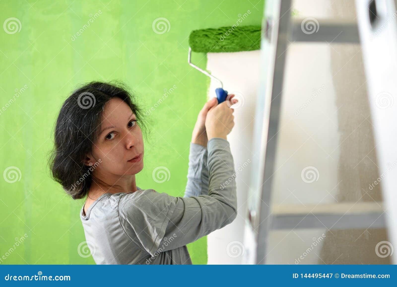 Pared interior de la mujer joven del verde bonito de la pintura con el rodillo en un nuevo hogar