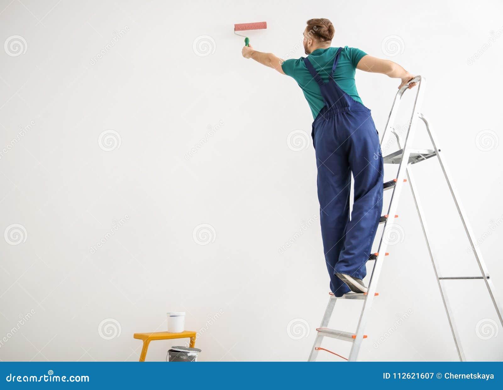 Pared masculina joven de la pintura del decorador