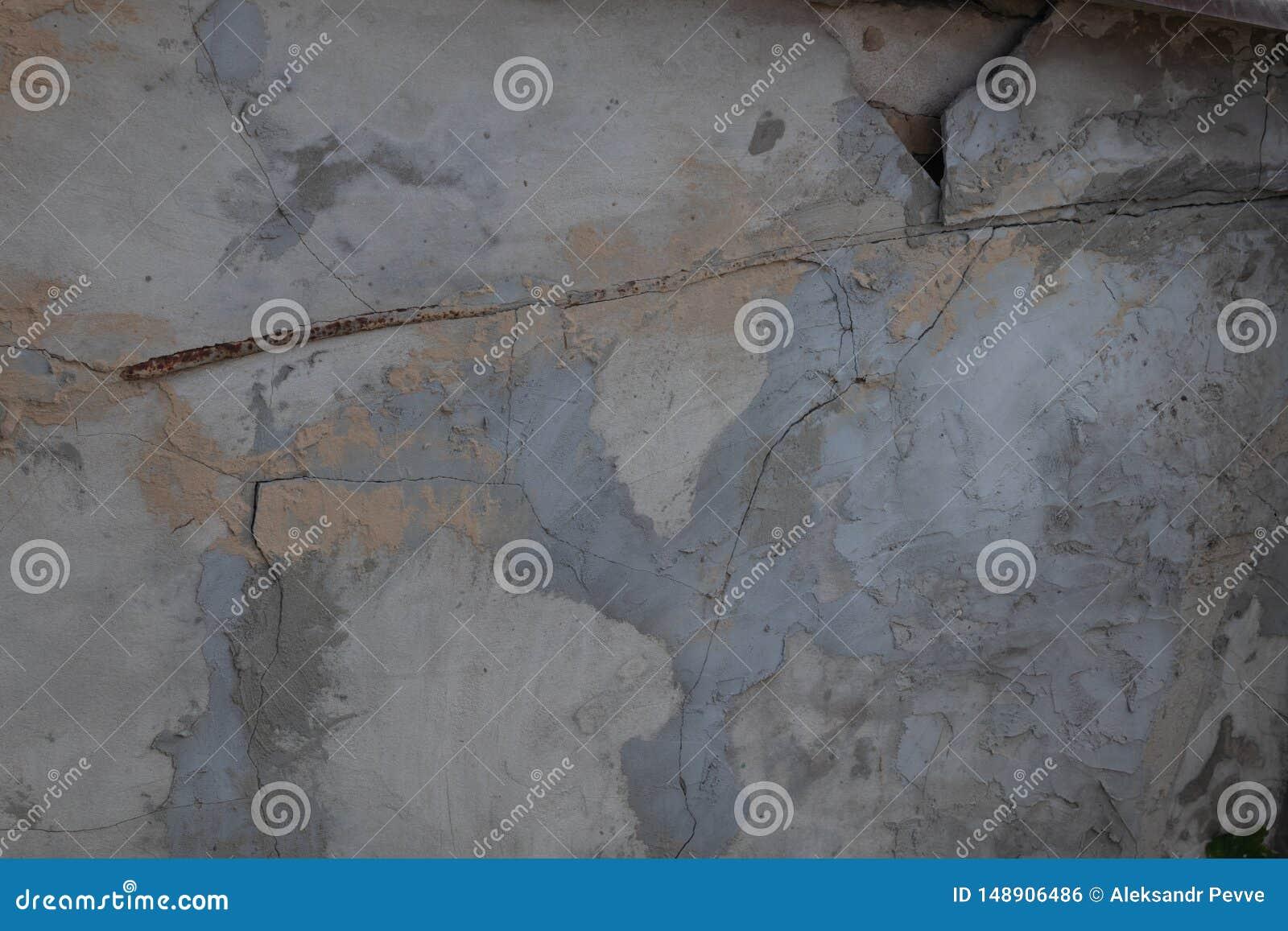 Pared rota y agrietada de un edificio viejo enyesado con el cemento