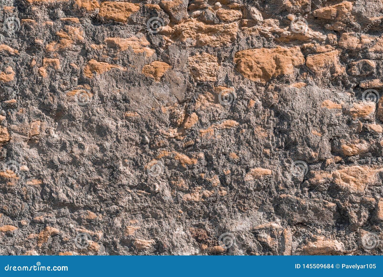 A parede ? feita da pedra e do cimento naturais desiguais