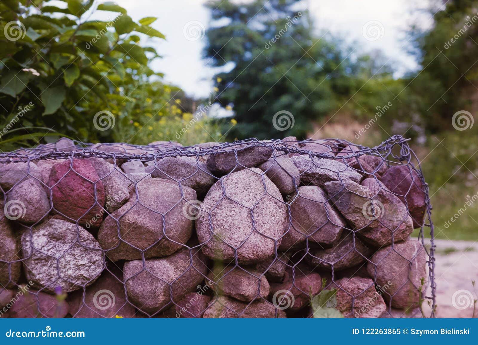 A parede com pedras entrelaçou-se com uma rede do metal