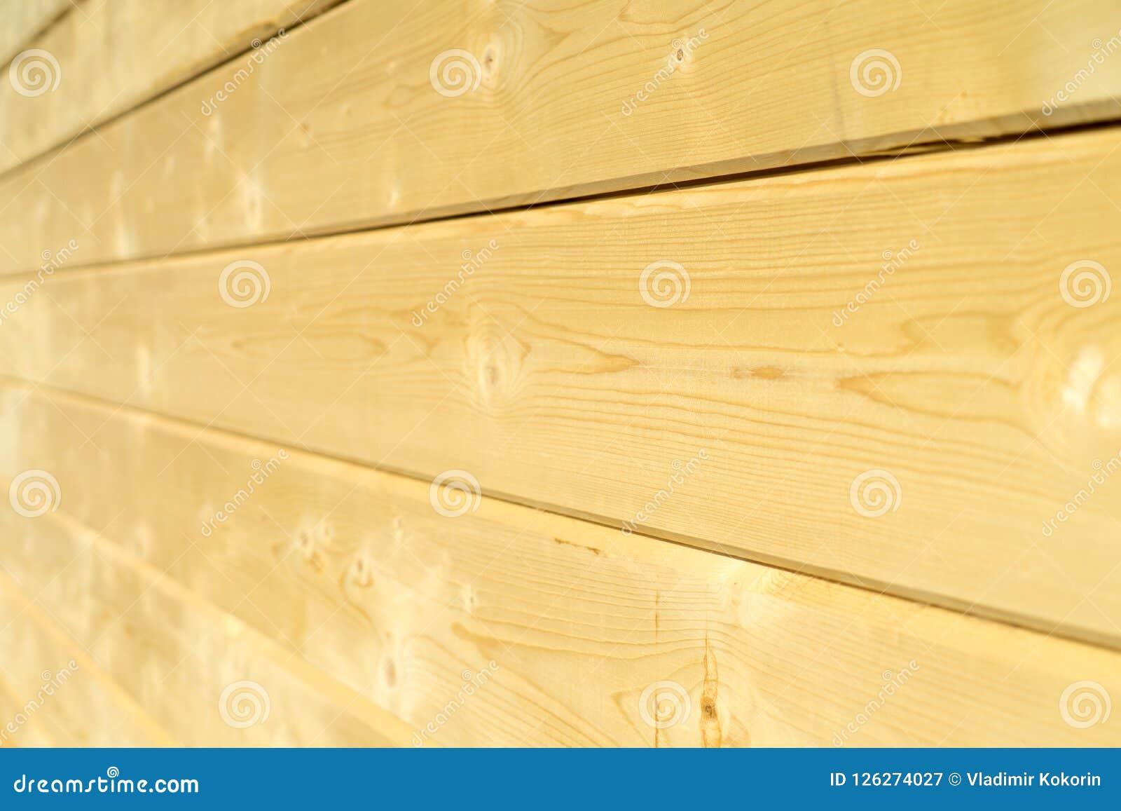 Parede da foto de uma casa de madeira feita de feixes de madeira