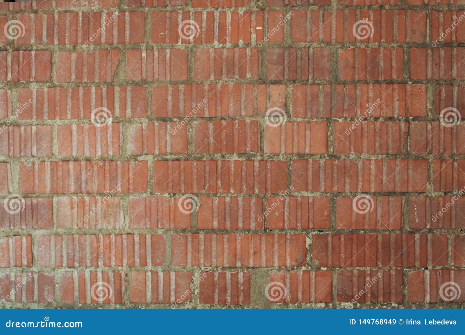 Parede da rua dos tijolos vermelhos gravados com as paredes desiguais