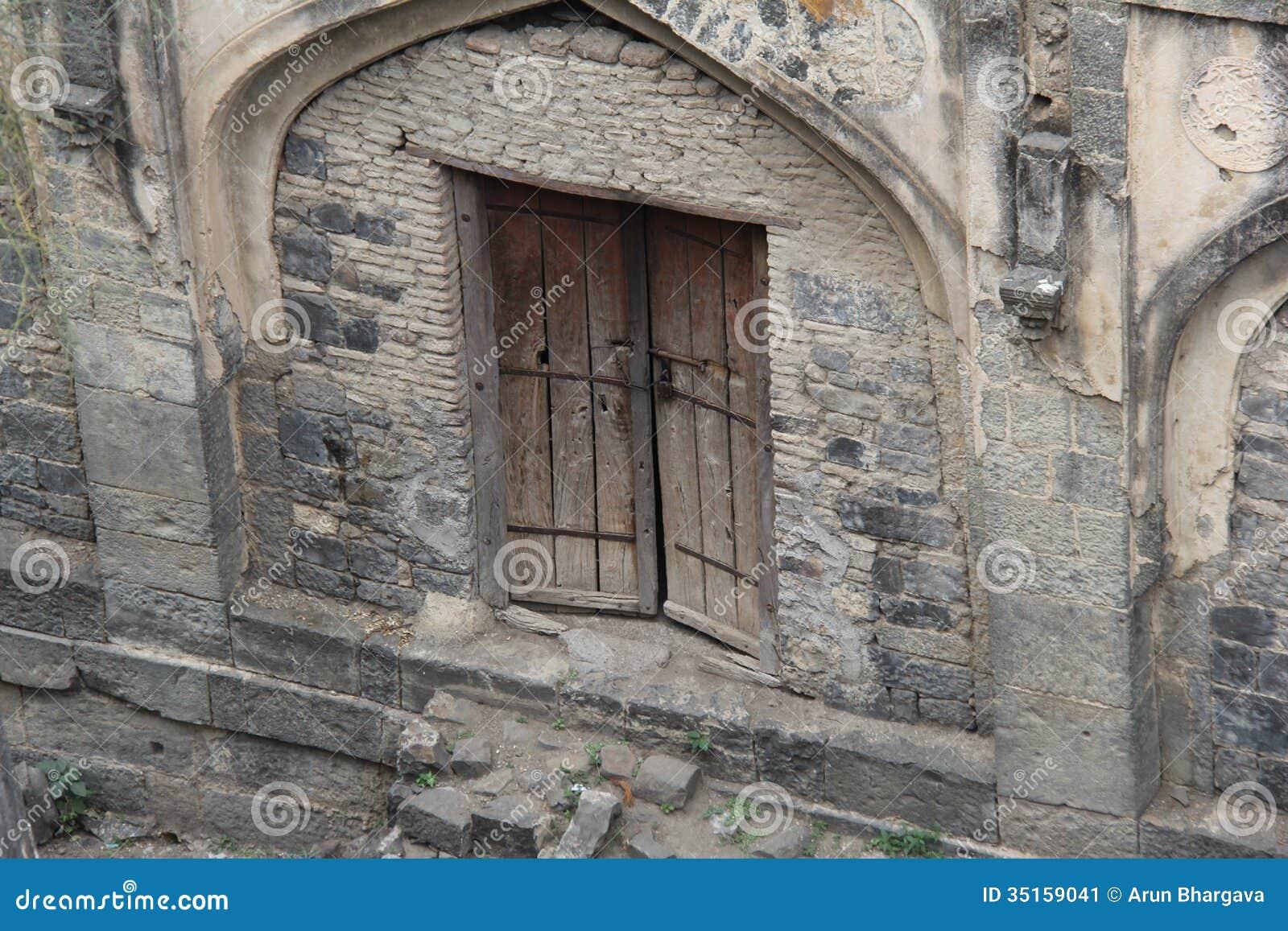 Parede de pedra arqueada com porta velha