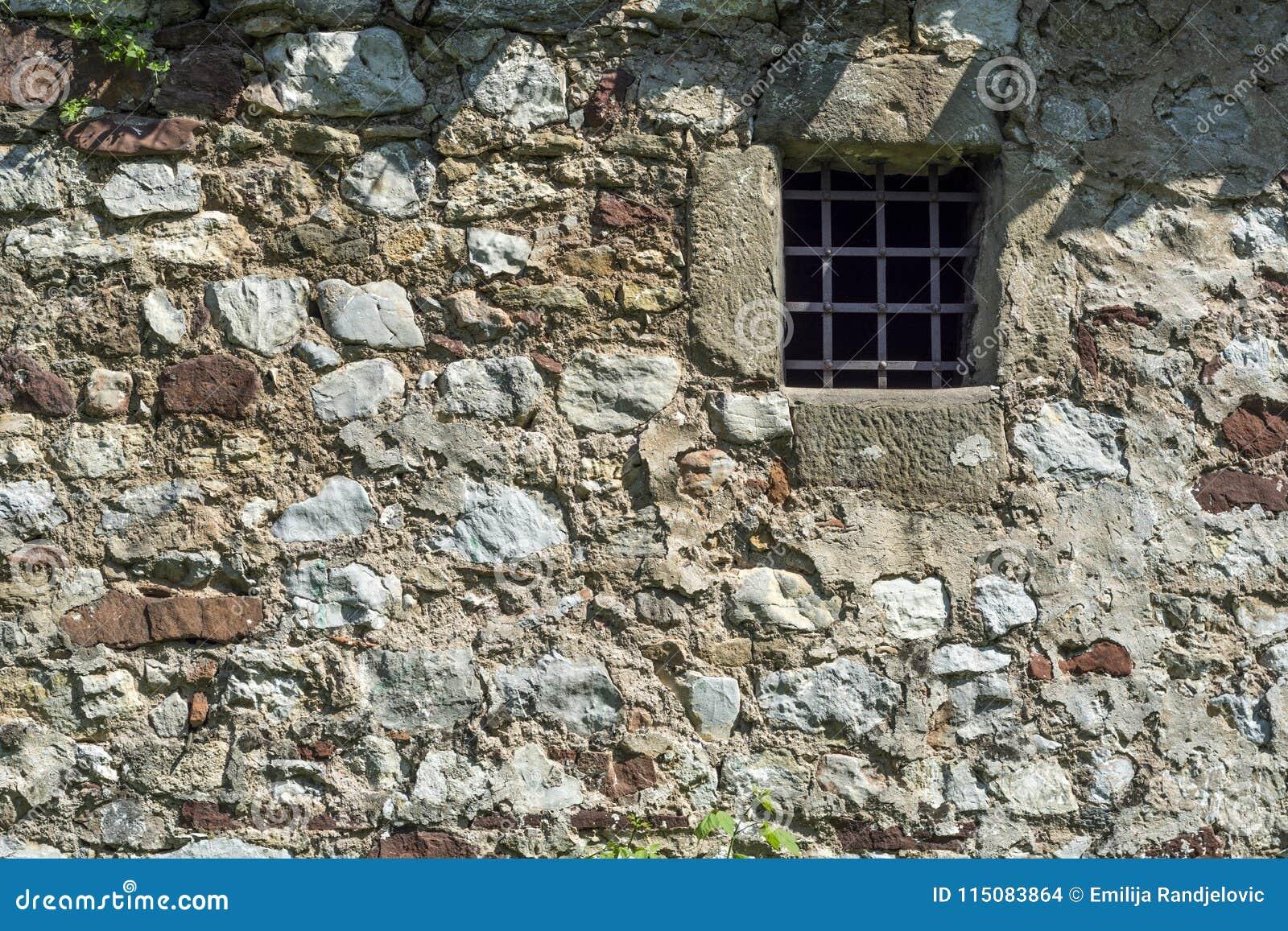 Parede de pedra da idade das trevas velha e janela pequena da cela com barras