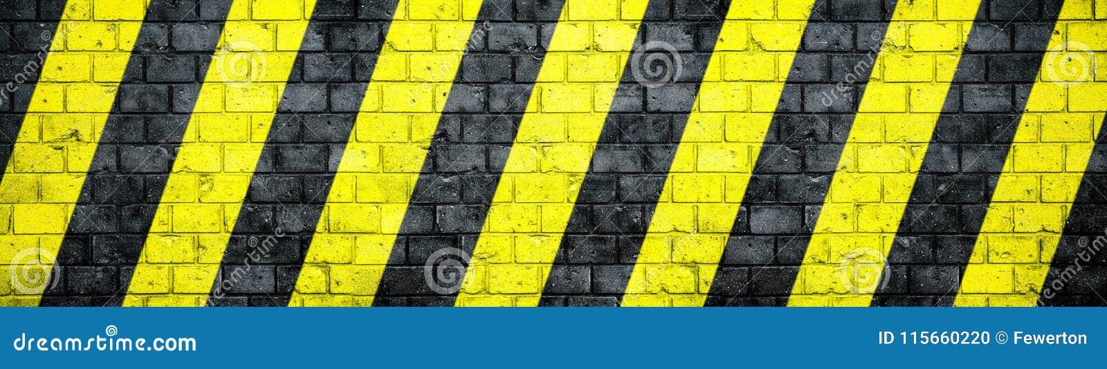 A parede de tijolo suja velha e resistida com as listras diagonais de advertência pretas e amarelas do perigo ou da atenção textu
