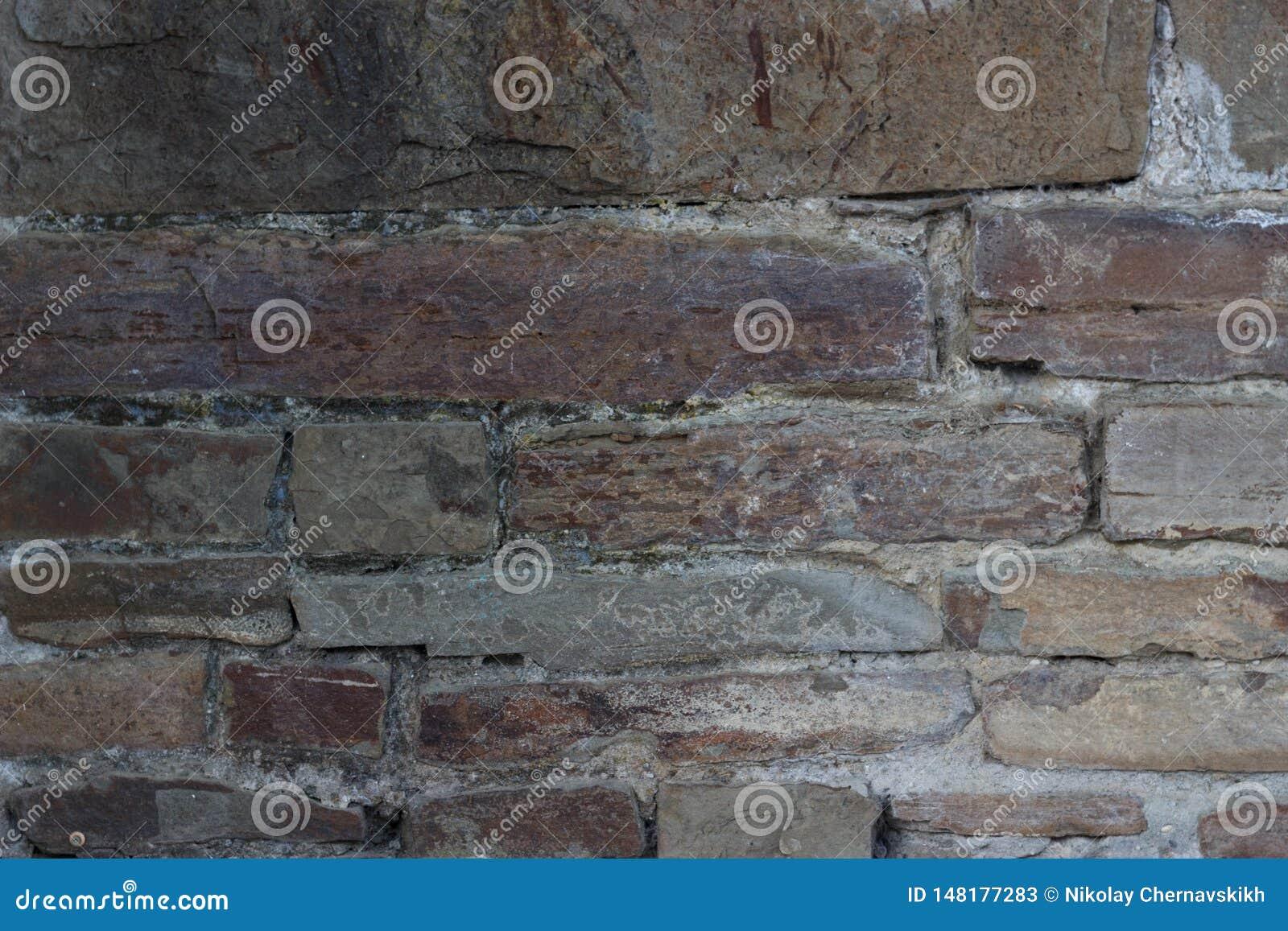 A parede de tijolo velha textured pedras escuras de tijolos diferentes das cores com cimento